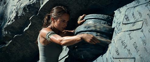Alicia Vikander as Lara Croft turning alarge, stone puzzle wheel.